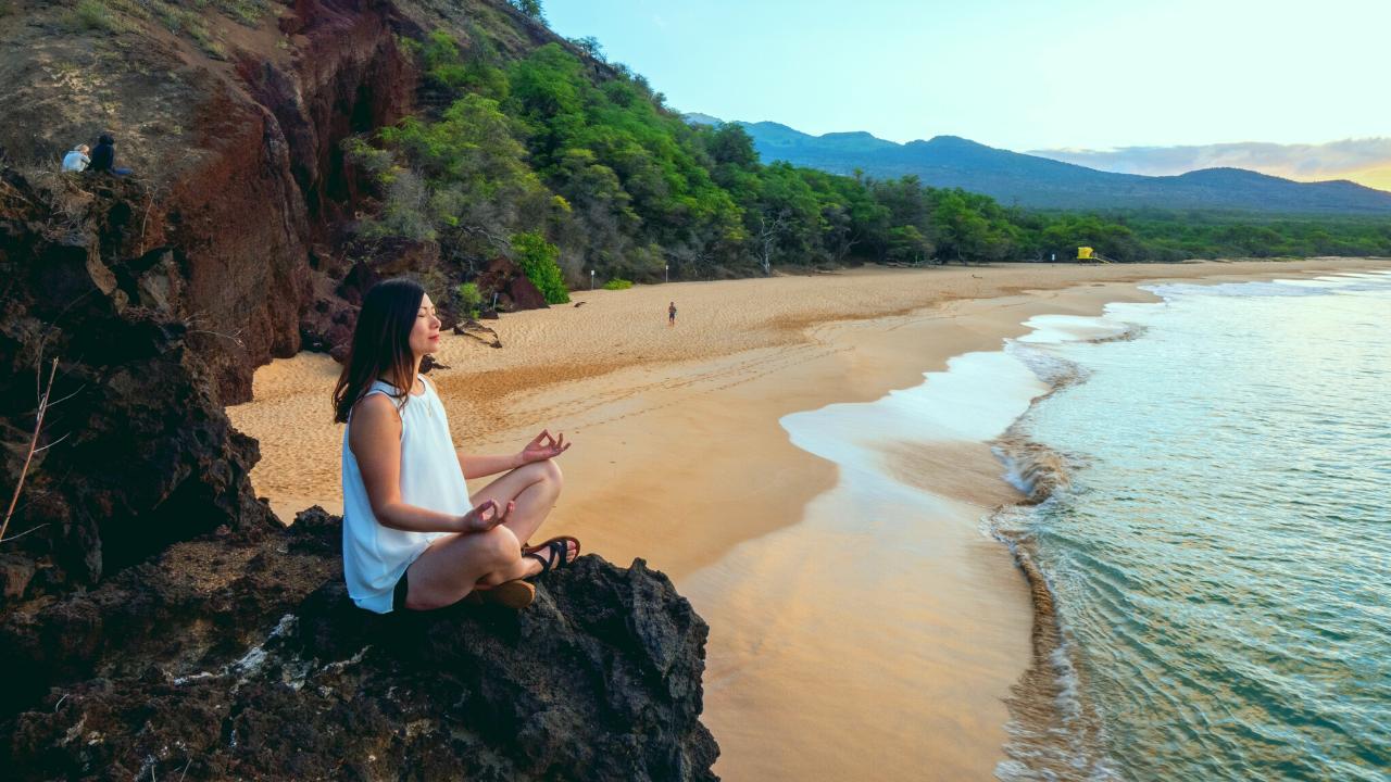woman meditating on rock in beach
